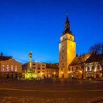 Abendaufnahme des Dreifaltigkeitsplatzes mit Dreifaltigkeitssäule und Stadtturm in Trnava