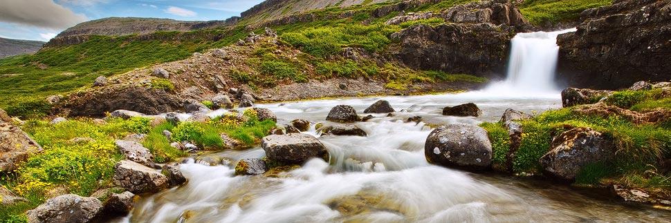 Landschaft mit kleinem Wasserfall und Fluss in Island