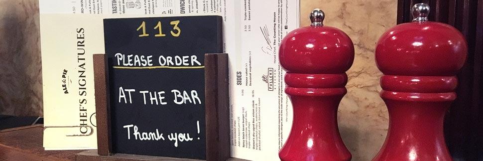 Hinweis zum Bestellen an der Bar in einem Pub in London